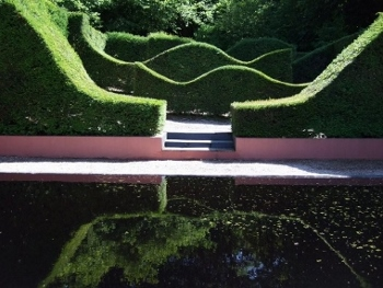 The picture shows the black pool, a popular feature of the gardens. Reflections in the water show the hedge line which is said to have been influenced by the outline of welsh hills.