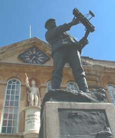 The picture shows the statue of Rolls outside the Shire hall, he holds a bi-plane